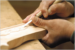 Craftman curving decorative pattens on the wood